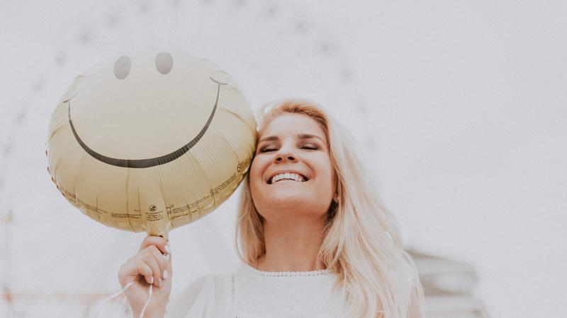 canva-woman-holding-a-smiley-balloon